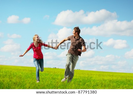 Young happy family running on a green meadow