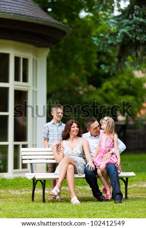 Young happy family sitting in the sun in front of their new home on a bench - it is a villa - stock photo