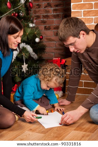 Young happy family sitting near Christmas tree - stock photo