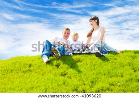 Young happy family sitting on the spring grass - stock photo