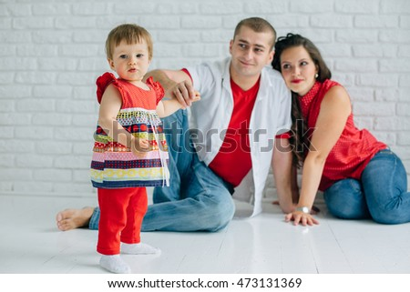 Young happy family sitting on the white floor and having fun. Parents with baby little girl in colorful dress. Man and woman in jeans. Brick wall. Mother father daughter.