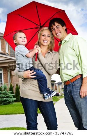 Young happy family under umbrella on sidewalk - stock photo
