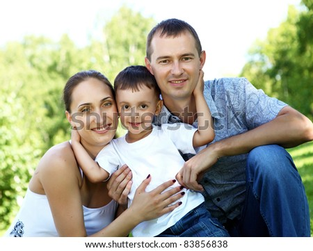 Young happy family with a child in the summer park - stock photo