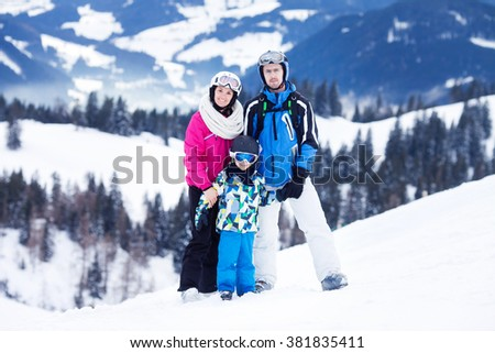 Young happy family with one child, skiing in the mountains, wintertime - stock photo
