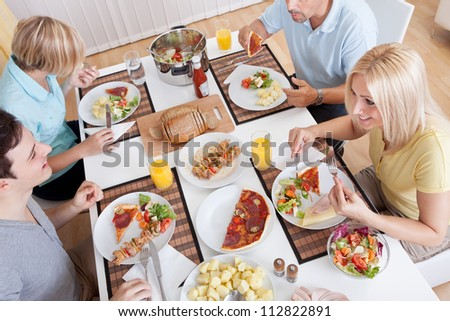 Young happy family with teenage children sitting down to eat a cold lunch of meat and salads - stock photo