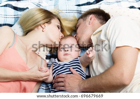 Young happy family with their infant boy laying on the floor
