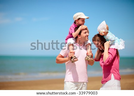 Young happy family with two kids on beach vacation - stock photo