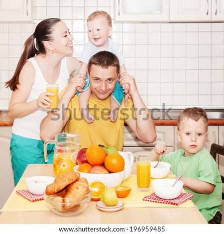 Young happy family with two small kids having breakfast in kitchen