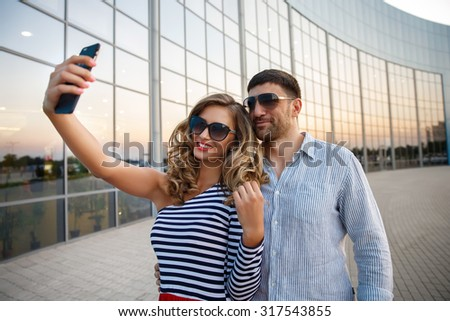 Young happy fashion couple in casual clothing with dark sunglasses taking selfie with a smart phone near the glass windows of the shop or cafe, summertime vacation  - stock photo