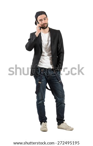 Young happy fashion model talking on the cellphone wearing cap backwards. Full body length portrait isolated over white background.  - stock photo