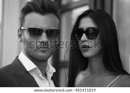 Young Happy fashionable couple in the city in stylish sunglasses.The man Wearing in business suit, the woman in romantic sexy dress with lace and coat