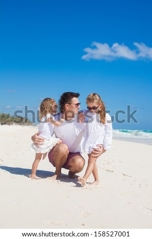 Young happy father and cute daughters having fun on white beach