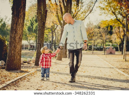 young happy father and his beautiful little 2 years old son walking together on Autumn park with trees having fun playing and sharing a sunny day in family love and childhood concept  - stock photo
