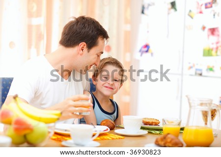 Young happy father and son having breakfast together - stock photo