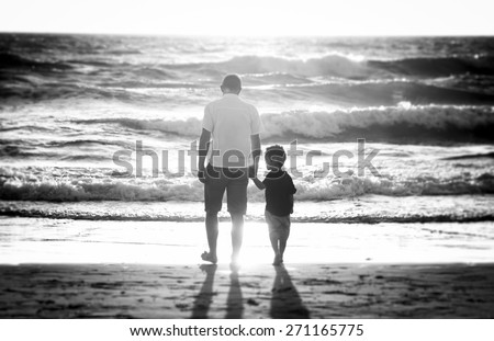 young happy father holding hand of his little son walking on the beach with barefoot in sand in front of sea waves, the kid together with dad looking to water in Summer sunset coast black and white - stock photo