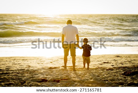 young happy father holding hand of his little son walking on the beach with barefoot in sand in front of sea waves, the kid together with dad looking to the water in Summer sunset coast - stock photo