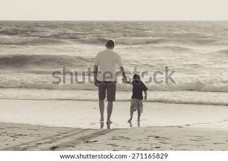 young happy father holding hand of his little son walking on the beach with barefoot in sand in front of sea waves, the kid together with dad looking to water in Summer sunset coast black and white