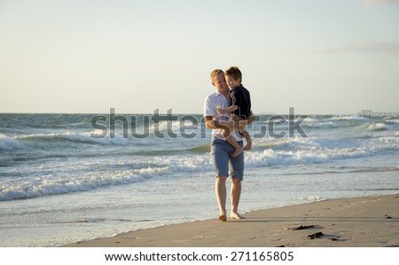 young happy father holding in his arms little son walking on the beach with barefoot in sand in front of sea waves, the kid smiling and having fun together with dad in Summer vacation concept