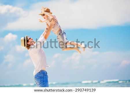 Young happy father holding little son in his arms putting him up standing barefoot at the beach with ocean and beautiful clouds on background. Having fun with the kid in summer coast - stock photo