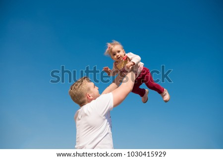 Young happy father holding up his daughter in air against sky.