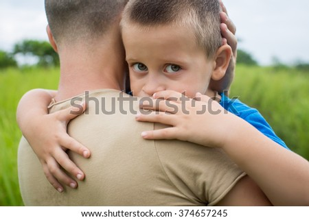 young happy father holding up in his arms little son - stock photo