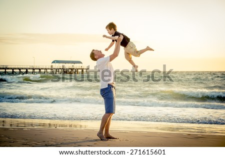 young happy father holding up in his arms little son putting him up at the beach in barefoot standing in front of sea waves wet sand having fun with the kid in Summer sunset coast - stock photo