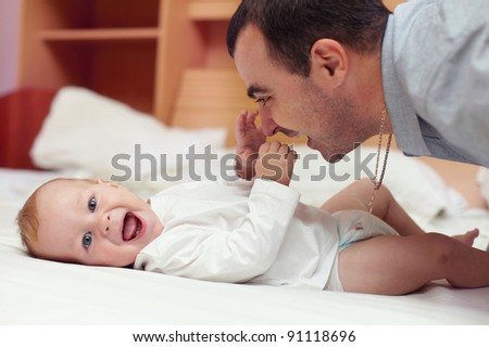 Young happy father playing  with baby lying in bed. baby want to catch father's face
