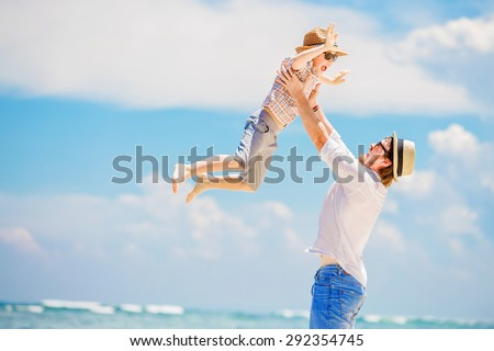 Young happy father playing with his little son standing barefoot at the beach with ocean and beautiful clouds on background. Having fun with the kid in summer coast on holidays - stock photo