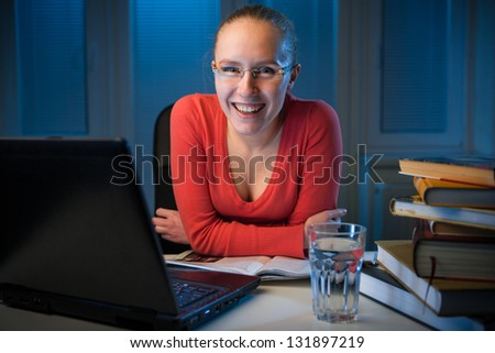 young  happy female college student smiling behind her table on a late evening,  funny night procrastination concept