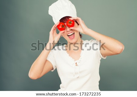 young happy female cook holding tomatoes on her eyes - stock photo
