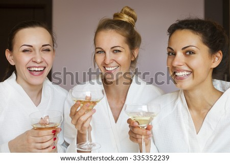 Young happy female friends drinking champagne in spa and have fun