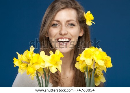 Young happy female holding bunches of flowers isolated on blue background - stock photo