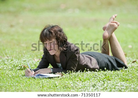 young happy female in blue shirt makes some notes in notepad, - stock photo