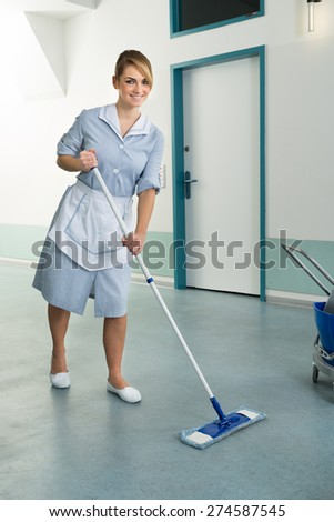Young Happy Female Janitor Cleaning Floor Of Corridor Pass - stock photo