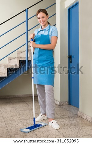 Young Happy Female Janitor Standing With Mop In Corridor - stock photo