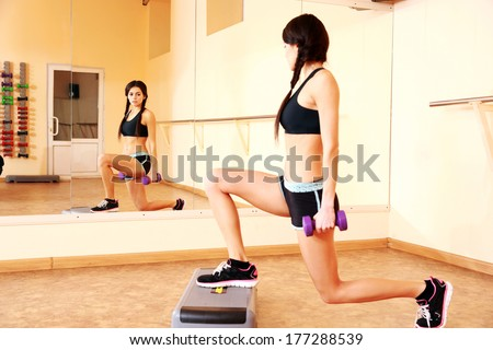 Young happy fit woman doing exercises with dumbells on step board and looking on her reflection in mirror at gym - stock photo