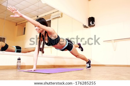 Young happy fit woman doing fitness exercises at gym - stock photo