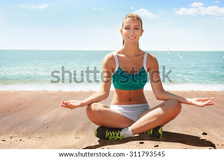 Young happy fitness woman relaxing after workout on sea shore  - stock photo