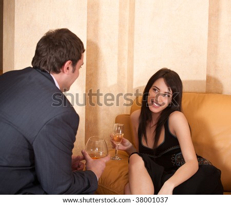Young happy flirting couple with alcohol drinks in cafe - stock photo
