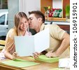 Young happy flirtive couple with menu in caf�© - stock photo