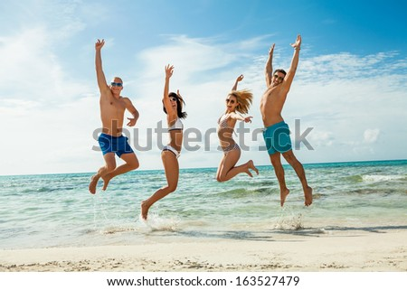 young happy friends have fun on the beach summer holidays lifestyle - stock photo