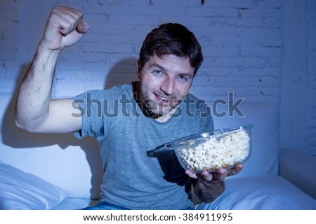 young happy fun sitting at living room couch watching sport match on tv cheering his team gesturing victory fist smiling excited holding popcorn in broadcast television concept - stock photo