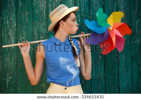 Young happy funny (vintage) dressed woman with colorful weather vane,looking like flower. Old green fence on the background. Picture ideal for illustating woman magazines. - stock photo