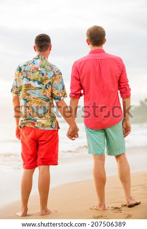 Young happy gay couple on the beach - stock photo