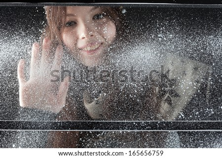 young happy girl behind snow window dark - stock photo