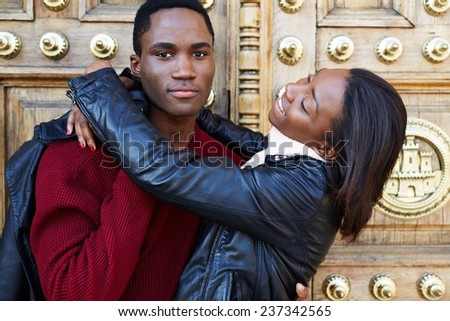 Young happy girl embracing her boyfriend standing on beautiful background outdoors, charming girlfriend embracing her boyfriend during vacation travel on honeymoon, lovely girl embracing her boyfriend - stock photo