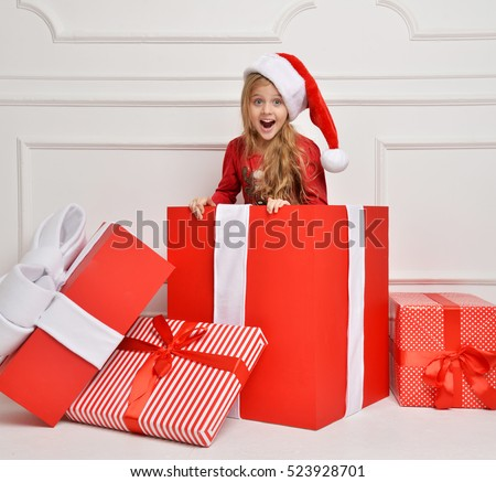 Young happy girl in Christmas Santa hat with big present gift smiling yelling  isolated on a white background. New year 2017 concept