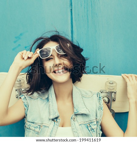 Young happy girl in sunglasses posing with skateboard. Lifestyle outdoor toned portrait - stock photo