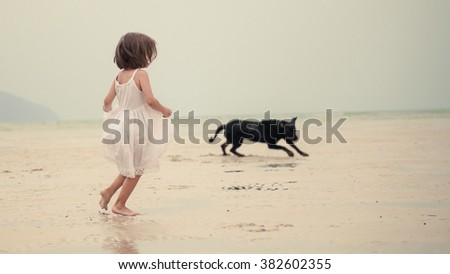 Young happy girl in white dress is running with the black dog on the tropical beach  - stock photo