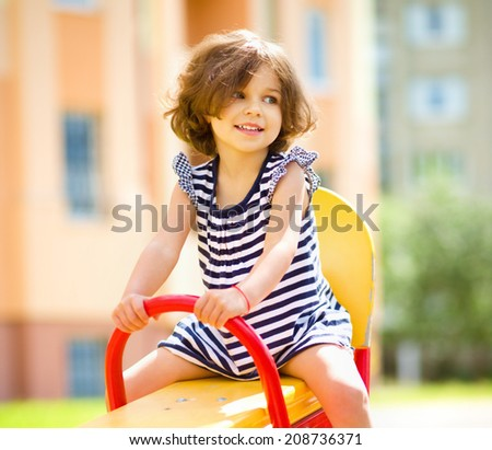 Young happy girl is swinging in playground, outdoor shoot - stock photo